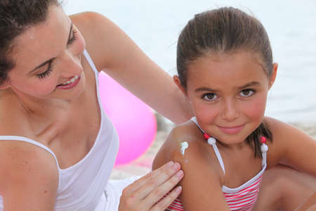sunscreen: Mother putting suncream on her daughter. Stock Photo