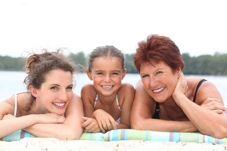 swimming costumes: a 30 years old woman, a little girl and a 55 years old woman lying down on the beach, behind sea and forest background