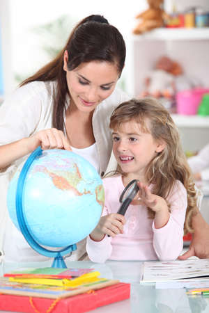 Mother and daughter looking at a globe with a magnifying glass photo