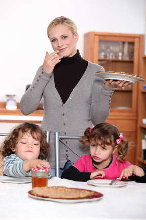 honey blonde: mother holding a dish of crepes and children waiting to eat crepes