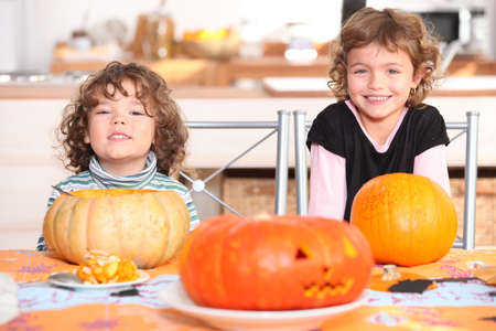 little boy and girl dressed in pajamas posing behind pumpkins Stock Photo - 11136659