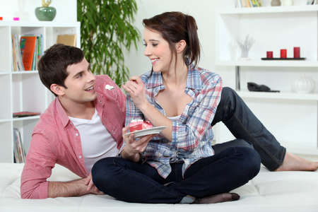 couple eating cake in bed photo