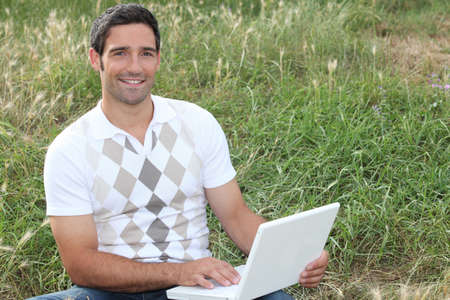 Man looking at his laptop in a field Stock Photo