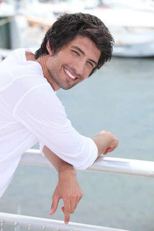 over shoulders: Man posing at the marina.