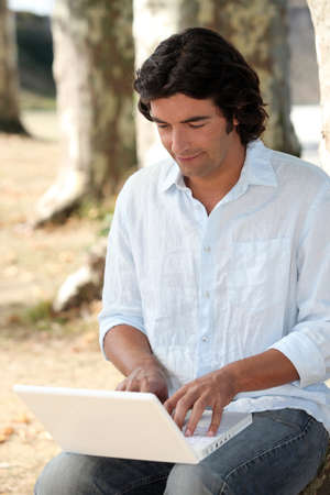 teleconference: Man in park using laptop