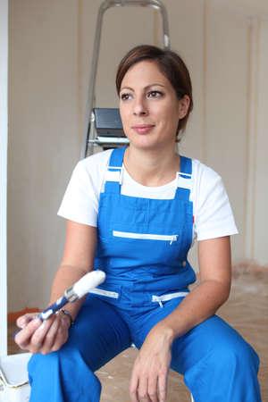 scaling ladder: Female painter sat on ladder