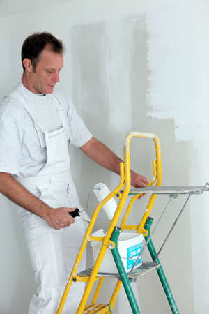 Man painting a room white photo