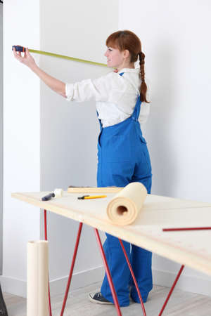 Female decorator measuring wall photo