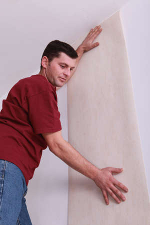 make a paste: Man wallpapering room