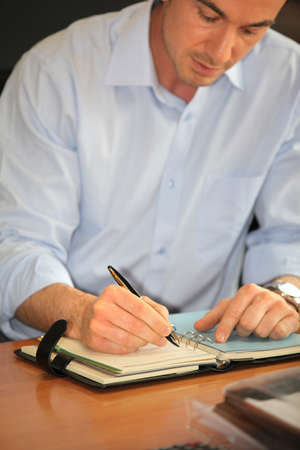 Man writing in a personal organizer photo