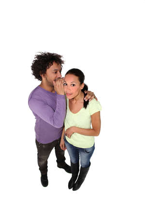 Man whispering secret to young woman photo