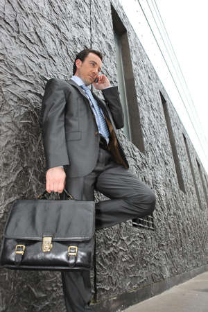 sidewalk talk: Businessman on the street with a briefcase and mobile phone Stock Photo