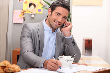 Man taking a business call over breakfast photo