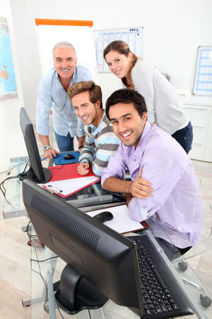 Four smiling people gathered round a computer in a classroom photo