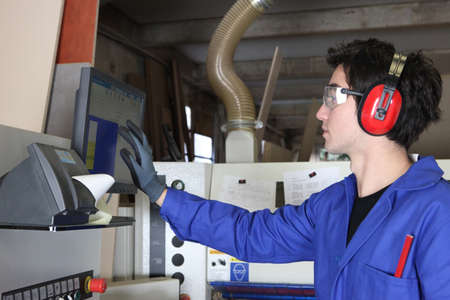 anti noise: Young man operating factory machinery