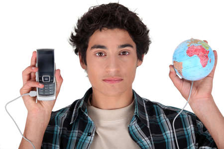 auscultate: a teenage boy connecting a cell phone and a globe
