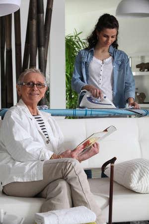 haushaltshilfe: Junge Frau Bügeln und ältere Frau sitzt auf einem Sofa