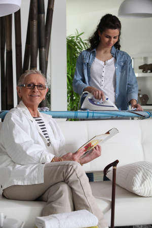 gospodarstwo domowe: Młody prasowania kobieta i starszy kobieta siedzi na kanapie