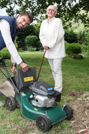 25 30 years old: Senior with gardener and lawnmower Stock Photo