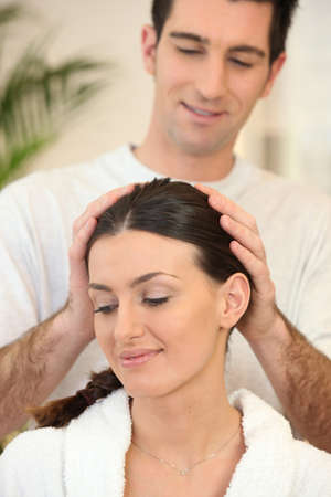 hairy arms: Man giving his wife a head massage Stock Photo