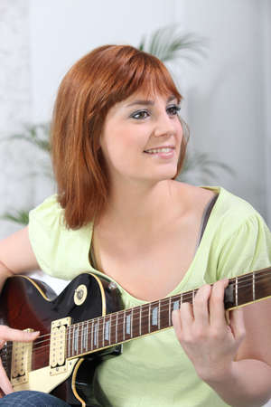Young woman playing a guitar at home photo