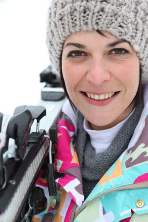 Woman resting skis on shoulder photo