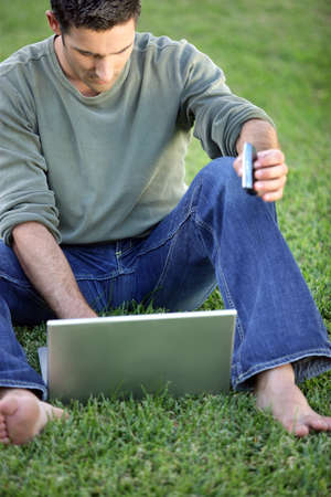 barefoot man: Man sat barefoot in filed with laptop