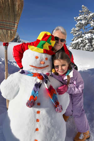 frosty the snowman: Father and daughter building snowman