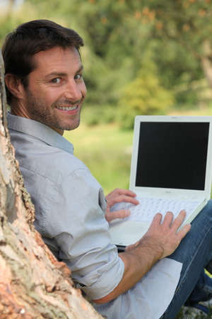 35 39 years: Happy man sitting outdoors using a laptop computer with a screen left blank for your image Stock Photo