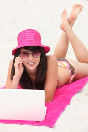 Young woman in a bright pink straw hat using her laptop computer on the beach photo