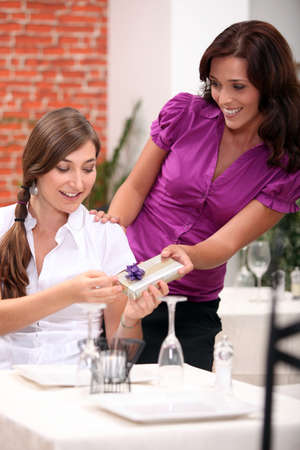 generous: a teenage girl receiving a gift at restaurant