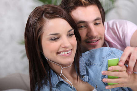Young couple with a personal music player photo