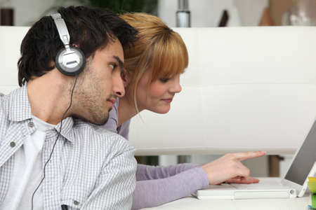 Boy listening to music and girl using laptop computer Stock Photo - 11135639