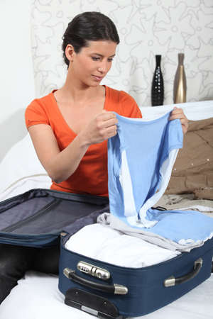 suitcase packing: Young woman packing her suitcase