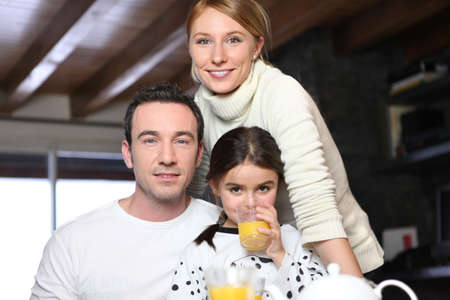 citrus family: Young girl drinking a glass of orange juice while posing for the camera with her parents