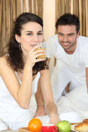 Couple enjoying breakfast in bed photo