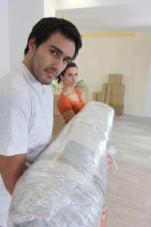 Couple carrying carpet photo