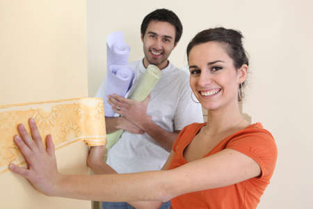 home remodel: Couple wallpapering Stock Photo