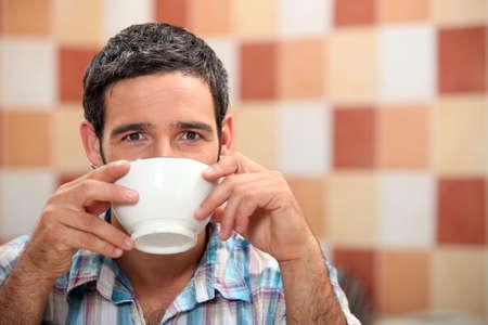 tomando café: El hombre de beber de un recipiente blanco en una cocina de azulejos