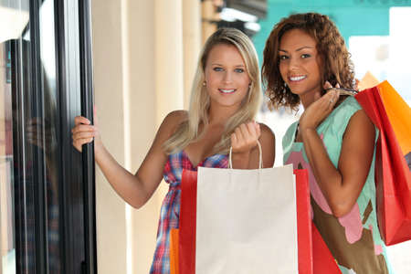 gastos: portrait of two girls with shopping bags