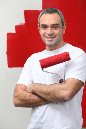 hombre pintando: hombre feliz de pintar la pared de su Foto de archivo