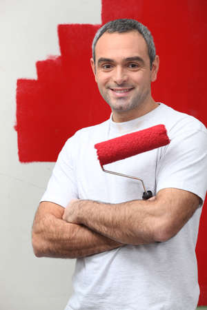 occupancy: man happy to paint his wall Stock Photo