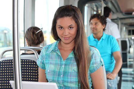 Young woman working on a laptop on a tram photo