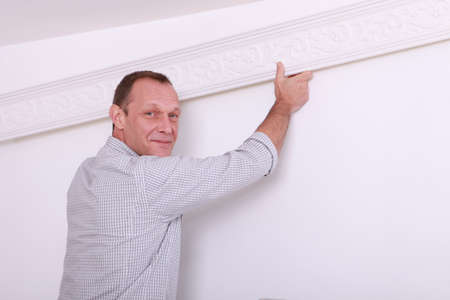moulded: Decorator fixing coving to a ceiling Stock Photo