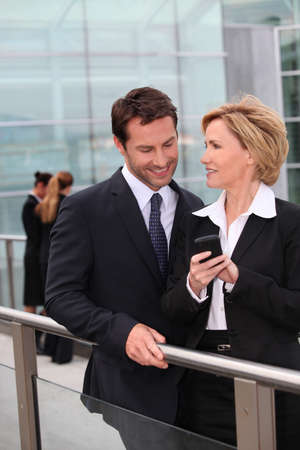 Businessman and businesswoman watching mobile phone outdoors Stock Photo - 11135970