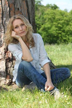 unwinding: Woman relaxing under a tree