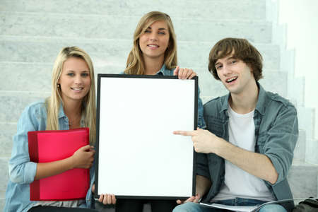 16 19 years: Three students holding a board left blank for your image