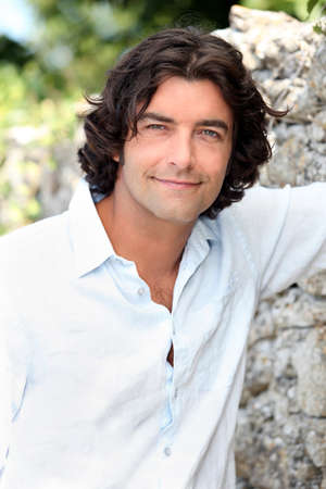 Handsome man with long hair standing by an old stone wall photo