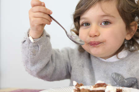 Young girl eating a piece of cake photo