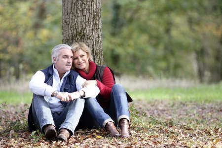mature couple: Married couple sat by tree Stock Photo